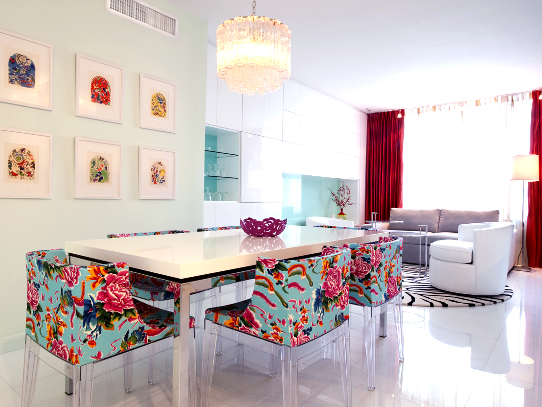 Dining room area with chandelier, bright colorful pink and blue chairs, large mirror on wall, and framed art panels on other wall.