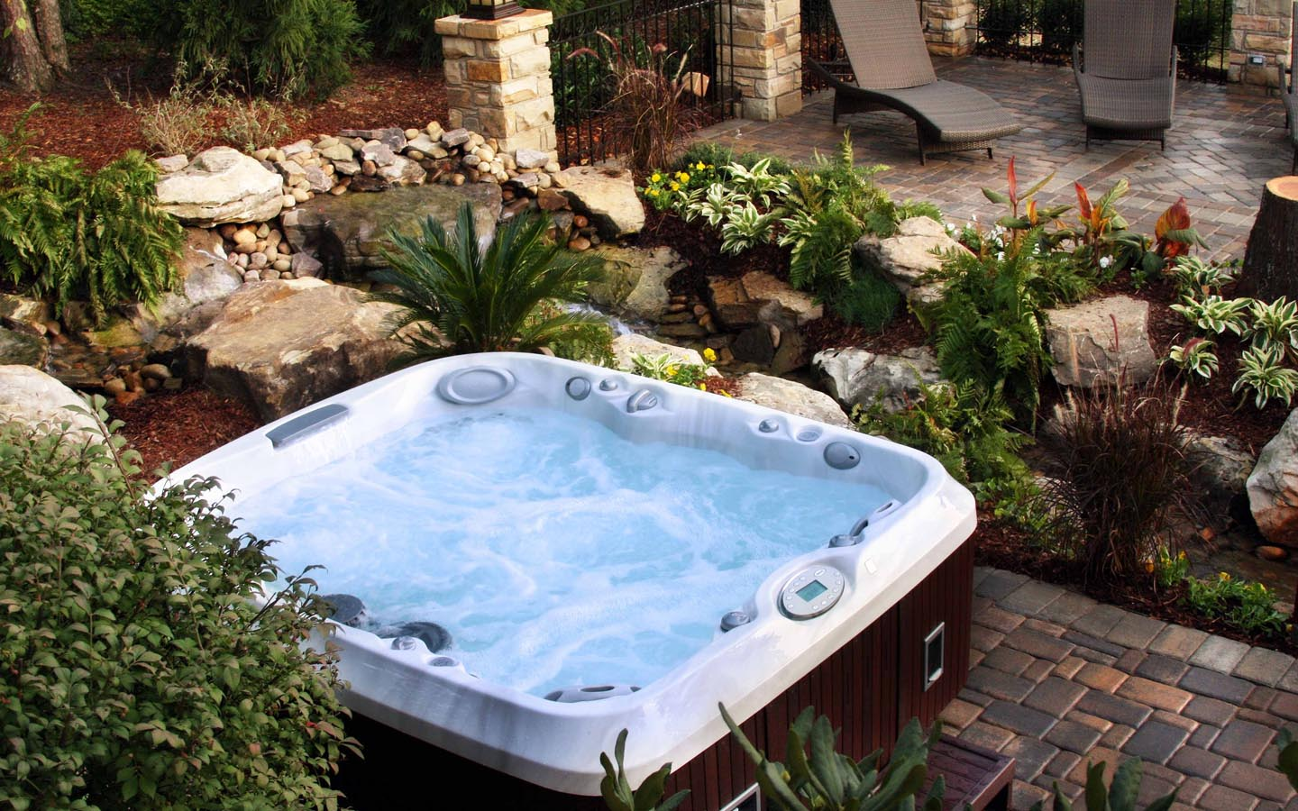 outdoor-wooden-clad-jacuzzi-upon-dark-stone-tile-floor-with-natural-greenery-surround
